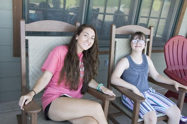Camp counselor and camper relax on patio